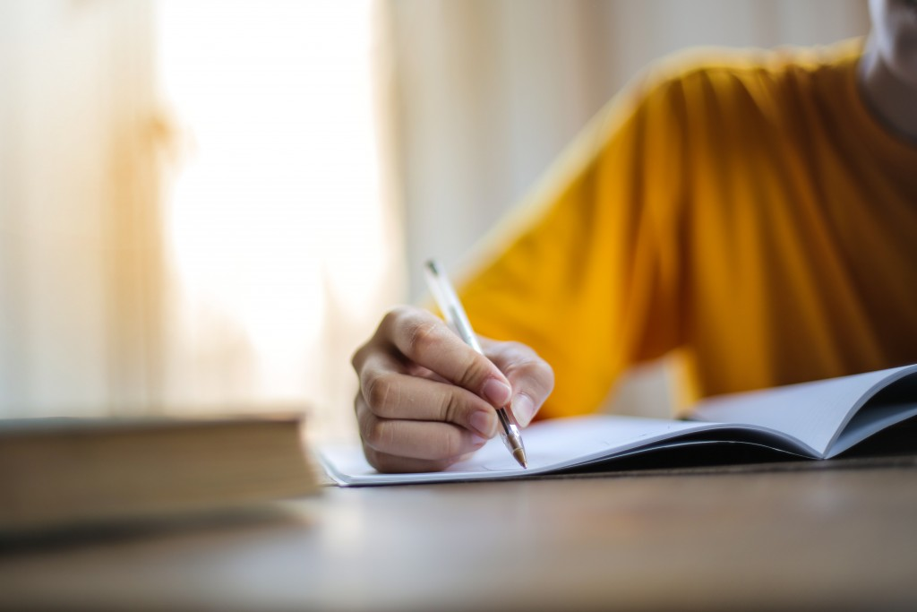 man writing down something in a notebook