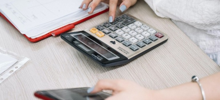 woman using a phone and calculator