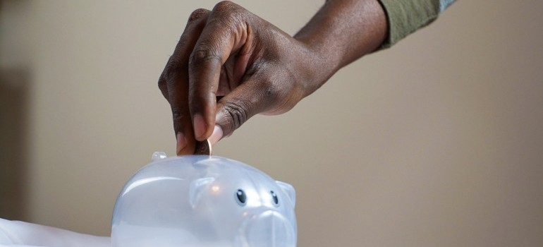 a hand holding coins and putting them in piggy bank