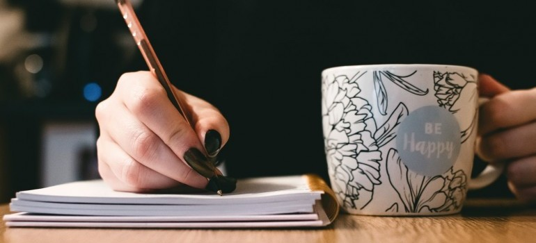 hand writting something down in a notebook and a cup