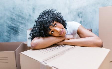 woman leaning on a cardboard box