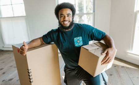A mover smiling and holding moving boxes.