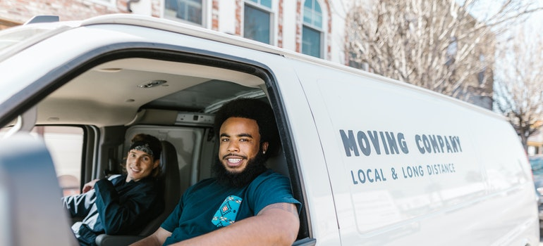 Two guys in moving van listen to what you have to ask your Canada movers
