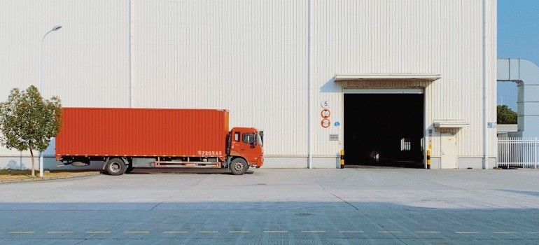 red truck in front of a white warehouse