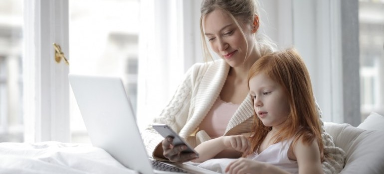 prepare your kids for a family move to Toronto like this mother and daughter lying in bed looking at something in the laptop and talking to each other