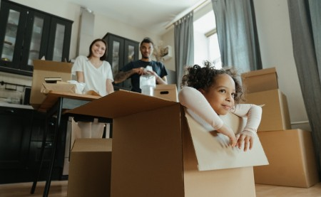 mom, dad and a child that is in a box in preparation for moving cross Canada with kids