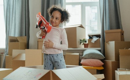 a girl standing in the box holding a red toy