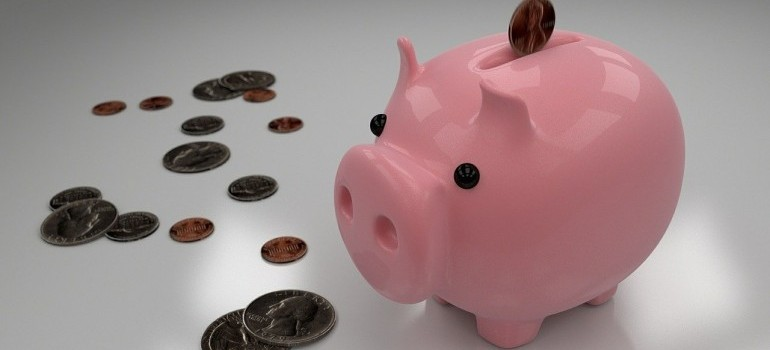 A piggy bank with coins around it.