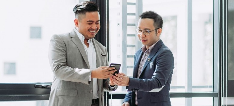 two people looking at a phone screen