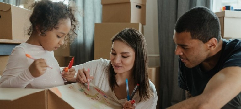 A family taking a break during packing for the move and drawing on the moving box