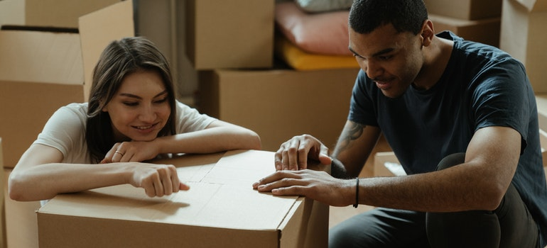 Man and woman packing things in cardboard box