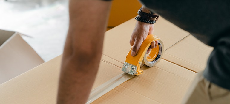 Man prepare cardboard box while moving Toronto to Fredericton New Brunswick