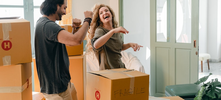 Man and woman having fun while packing for moving from Alberta to Ontario