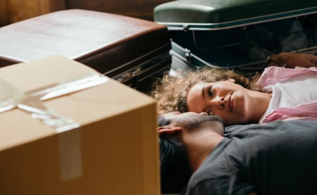 a couple lying on the floor taking a break from packing