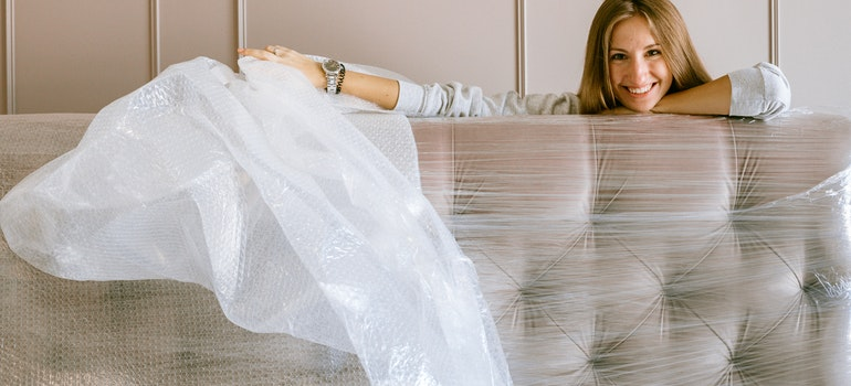 Women packing her sofa and smiling