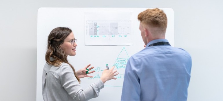 two people looking at a whiteboard