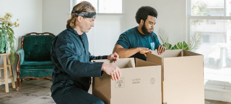 two movers packing cardboard boxes