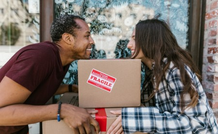 a young couple moving taking a break and looking at each other over a moving box