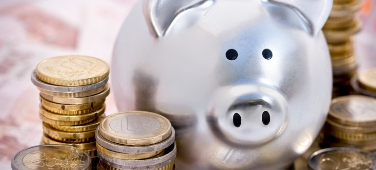A silver piggy bank and coins to use when moving from Saskatchewan to Ontario.