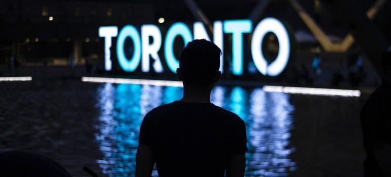 A man looking at a Toronto sign at night.