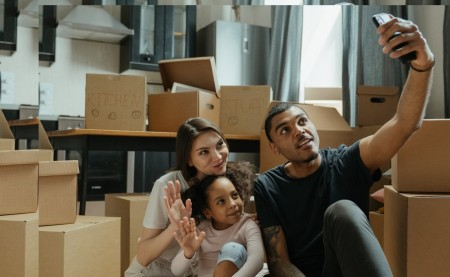couple with baby girl surrounded with moving boxes