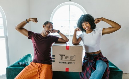 couple packing moving boxes and feeling strong